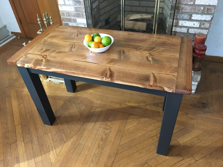 Small rustic wood farmhouse table with breadboard ends and black painted legs