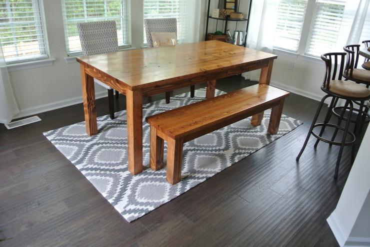 Custom farmhouse table and bench in sunroom on a grey rug