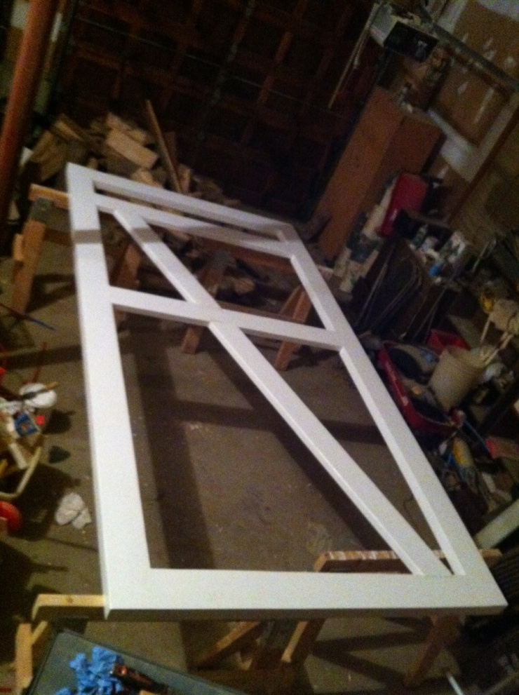 Diagonal braces being installed in a large wood barn door