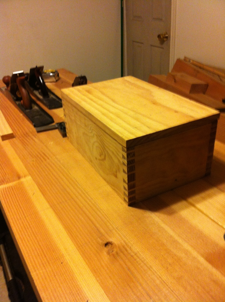 Wood box with dovetail joints on workbench.