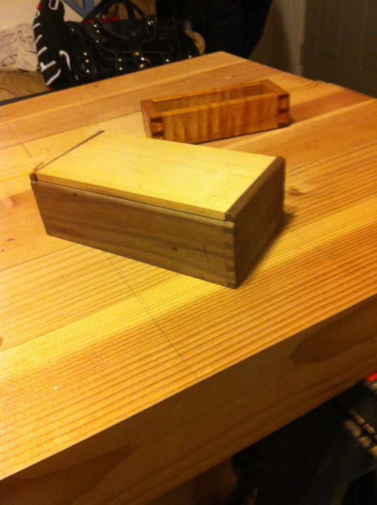 two small handmade wood boxes with dovetail joints on a workbench